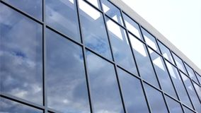 Glass facade with reflection of clouds stock video