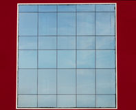 Glass facade. With sky reflected, on red wall Stock Images