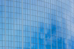 The glass facade of a skyscraper with a mirror reflection of sky windows. Photo Stock Images