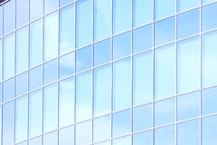 The glass facade of a skyscraper with a mirror reflection of sky windows Stock Images