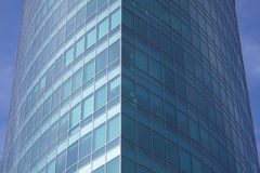 The glass facade of a skyscraper with a mirror reflection of sky windows Stock Image