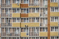 A glass facade with windows of a brick apartment building with loggias and balconies. Condominium with air conditioning royalty free stock images