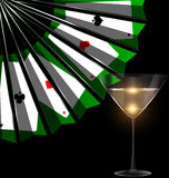 Glass, fan and cards. Dark background with the black green fan with image of cards and the glass of bubbles wine Stock Photos