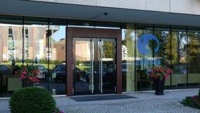 Glass fasad av en modern kontorsbyggnad med den Danone logoen Redaktörs- tolkning 3D Royaltyfri Bild