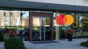Glass fasad av en modern kontorsbyggnad med den MasterCard logoen Redaktörs- tolkning 3D Arkivbild