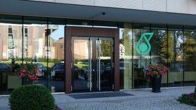 Glass fasad av en modern kontorsbyggnad med den Petroliam Nasional Berhad PETRONAS logoen Redaktörs- tolkning 3D Royaltyfria Foton