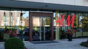Glass fasad av en modern kontorsbyggnad med logo för H M Redaktörs- tolkning 3D Arkivbilder