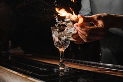 Glass of fiery cocktail on the bar counter stock images