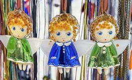 Glass figurines of angels in colorful dresses stock image