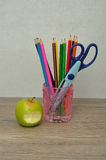 A glass filled with coloring pencils and a scissor Royalty Free Stock Photos