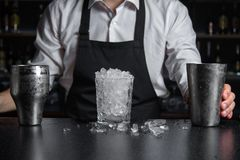 A glass filled full of crash ice and chilled shaker standing on. Close-up. A glass filled full of crash ice and chilled shaker standing on the bar counter royalty free stock images