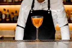 A glass filled with a golden alcholic drink. A glass filled with a golden alcoholic drink against the background of barman in a white shirt and bar counter Royalty Free Stock Images