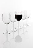 Glass filled with red wine in a row of empty glasses Royalty Free Stock Image