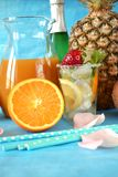 Glass filled up with ice and cocktail ingredients surrounded by orange, lemon, coconut and pineapple. Bottle of champagne in the background Royalty Free Stock Image
