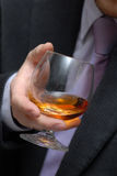 Glass the filled whisky. A glass the filled whisky in hands of the man Royalty Free Stock Photography