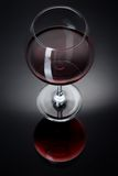 A glass filled with wine on a black table. A glass filled with wine on a black reflective surface Royalty Free Stock Image