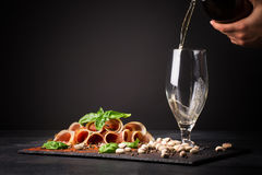 A glass filling with beer, pistachios and prosciutto seasoned with black pepper and basil on a dark background. Stock Photos
