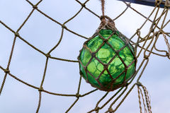 Glass fishing float ball with rope knots hanging in a fishing n Royalty Free Stock Photo