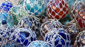 Glass Fishing Floats with Netting. Colorful glass fishing floats with netting. Glass floats provided buoyancy, but were sometimes lost and washed ashore Royalty Free Stock Images