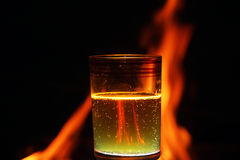 Glass of fizzy water infront of the fire Royalty Free Stock Images