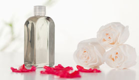 Glass flask with petals and roses Stock Photo