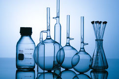 Glass flasks. Six glass objects used in Biomed labs on reflective background, backlit by blue light stock image