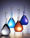 Glass flasks in color. 4 glass flasks filled with colored liquid and lit by a back light Stock Photos