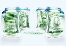 Glass flasks with money and three banknotes with coins Stock Photos