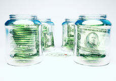 Glass flasks with money and three banknotes with coins. Wealth and poverty concept Stock Images