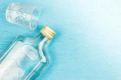 Glass and flat glass bottle on a blue. Background. Alcoholic beverages, vodka royalty free stock photo