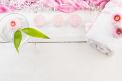 Glass with flower, pink candles and towel on wooden table Stock Photography