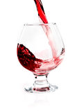 Glass with flowing wine. Isolated Stock Images