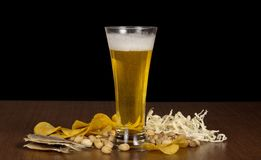 Glass of foamy beer with bubbles, chips, salty Royalty Free Stock Photos
