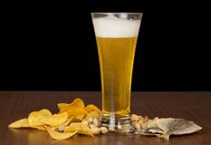 Glass of foamy beer with bubbles, chips, salty Royalty Free Stock Image