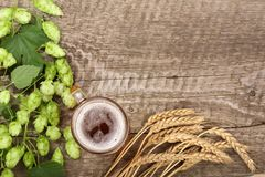 Glass of foamy beer with hop cones and wheat on old wooden background. Top view with copy space for your text Stock Photography