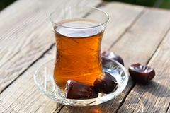 Glass of fragrant tea with dates Royalty Free Stock Photos