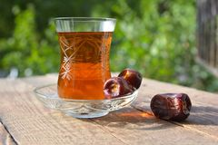 Glass of fragrant tea with dates Stock Images