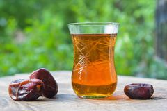 Glass of fragrant tea with dates Stock Photos
