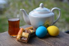 Glass of fragrant tea from teapot, pie and colorful eggs Stock Photography