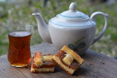Glass of fragrant tea from teapot, piece of pie with jam Stock Photos