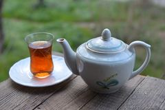 Glass of fragrant tea and teapot on table Royalty Free Stock Image