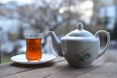 Glass of fragrant tea and teapot on table Royalty Free Stock Photo