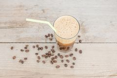 Glass of frappe coffee on wood background. Greek Frappe coffee. And coffee beans Stock Image
