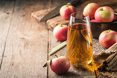 Glass of fresh apple juice. With red apples on wooden table stock photo