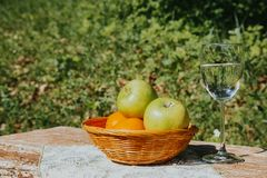 A glass of fresh Apple water and apples in a basket on a wooden table royalty free stock photography