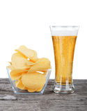 Glass of Fresh Beer and bowl of with Pile potato chips Royalty Free Stock Image