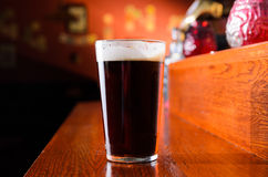 Glass of fresh beer on counter in pub. Glass of fresh beer on pub table Royalty Free Stock Image