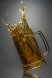 Glass of fresh beer fell on a reflective surface Royalty Free Stock Photography