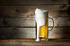 Glass of fresh beer with foam smudges. On wooden background Stock Photo