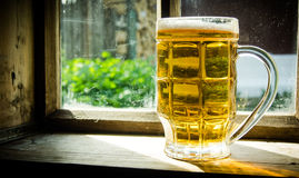 Glass of fresh beer on old wooden window sill . Royalty Free Stock Photo